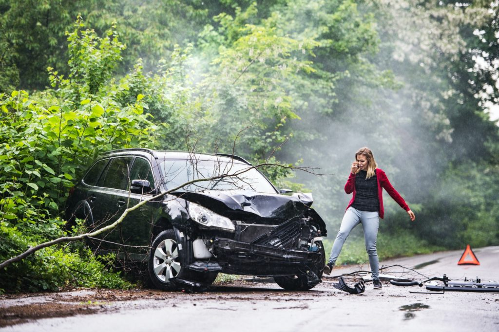 An angry young woman with smartphone by the damaged car after a car accident.